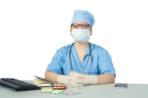 医療マスクのテーブルに座っている女性医師