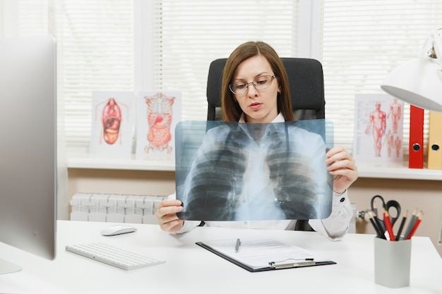 Female doctor sitting at desk, working on computer, holding x-ray of lungs, fluorography, roentgen in light office in hospital