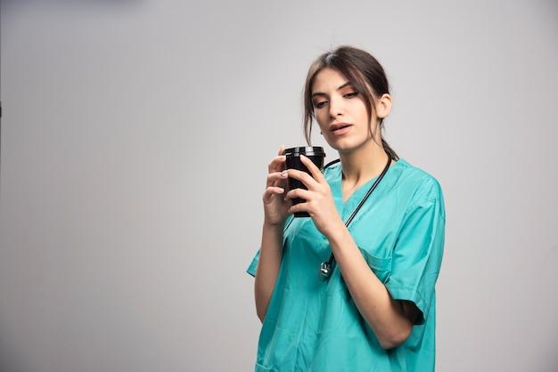 Женщина-врач чувствует запах кофе на сером