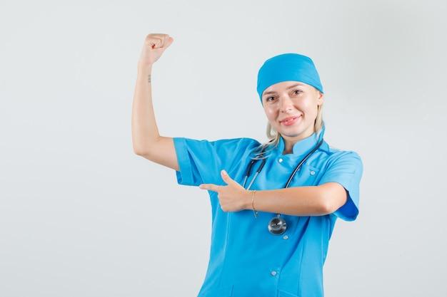Medico femminile che sorride e che indica al muscolo in uniforme blu e che sembra fiducioso