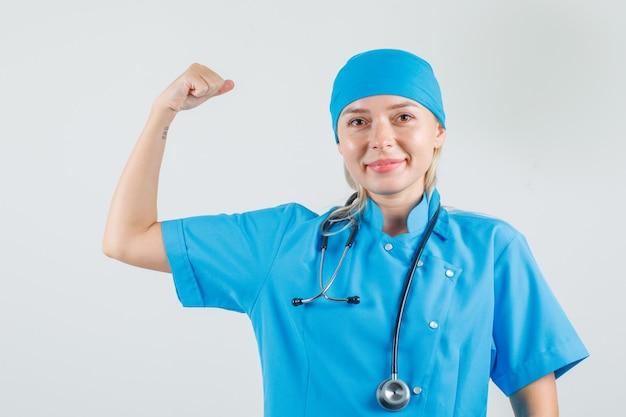 Medico femminile che sorride e che mostra il muscolo in uniforme blu e che sembra fiducioso