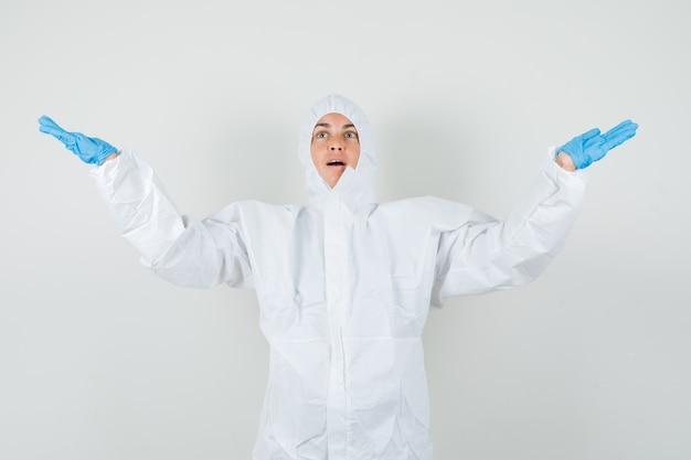 Medico femminile che diffonde le braccia in tuta protettiva