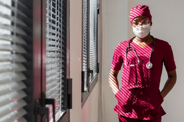 Female doctor standing next to hospital  windows