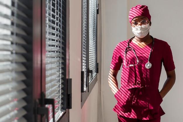 病院の窓の隣に立っている女性医師