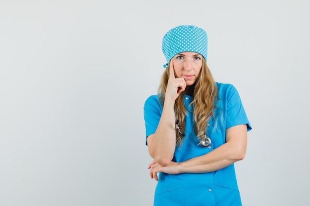 Dottoressa in piedi nel pensiero posa in uniforme blu e sembra intelligente