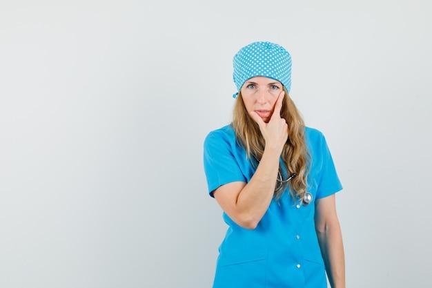Dottoressa in piedi nel pensiero posa in uniforme blu e sembra ragionevole.