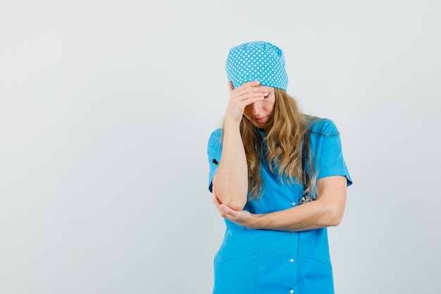 Medico donna in piedi nel pensiero posa in uniforme blu e sembra stanco.