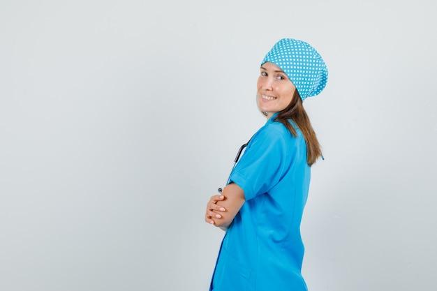 青い制服を着て腕を組んで立っている女医師。