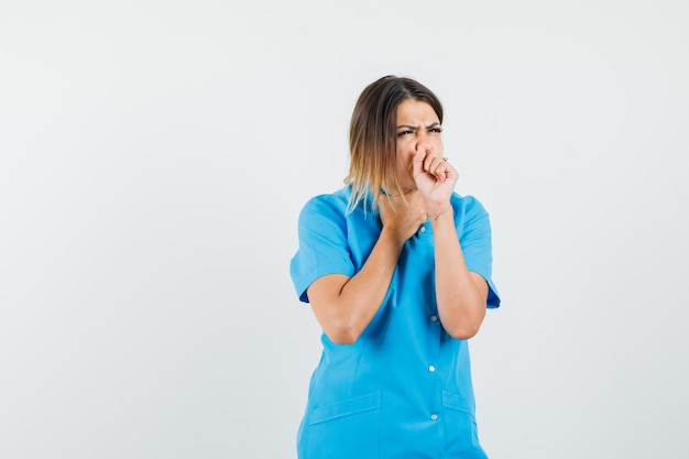Dottoressa che soffre di tosse in uniforme blu e sembra malata