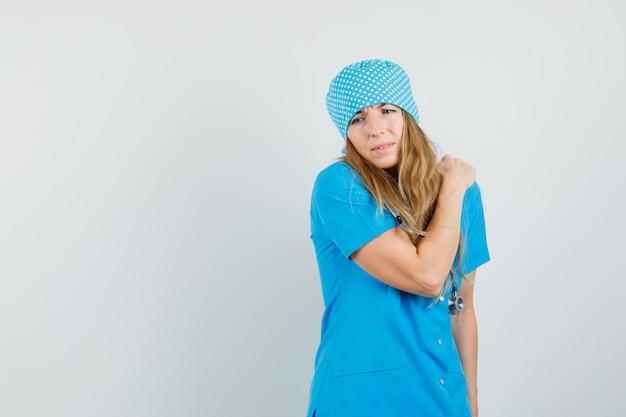 파란색 유니폼에 어깨 통증으로 고통 받고 피곤 찾고 여성 의사.