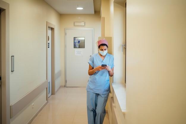 Female doctor surgeon using smart phone