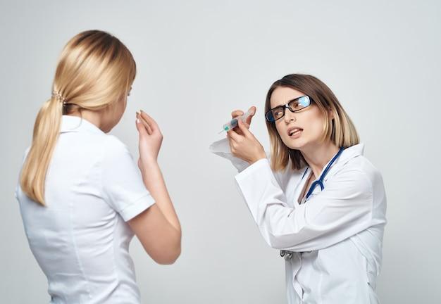 손 치료 밝은 배경에서 여성 의사 주사기