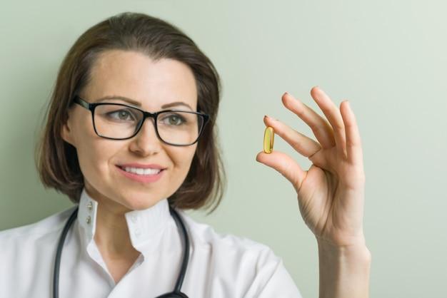 Female doctor takes vitamin capsule.