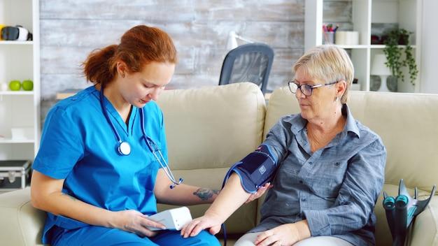 Female doctor taking blood pressure of senior woman in nursing home sitting on sofa