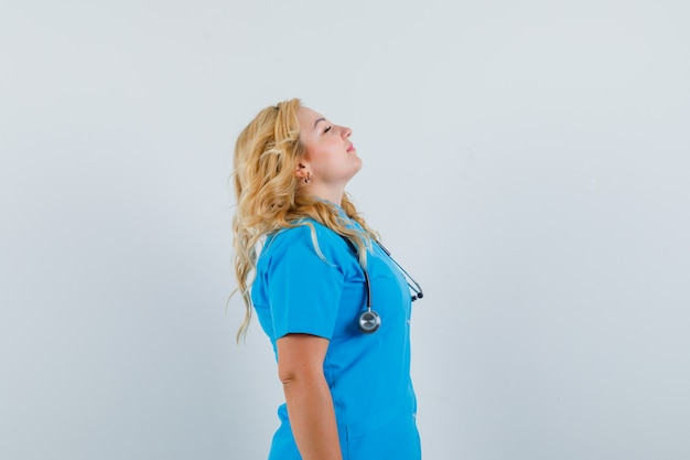 Female doctor taking a deep breath in blue uniform and looking relaxed. .