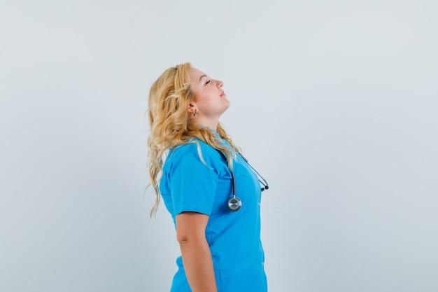 Medico femminile che prende un respiro profondo in uniforme blu e sembra rilassato. .