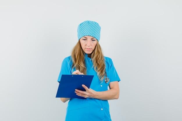 女医が青いユニフォームでクリップボードにメモを取り、忙しい探して