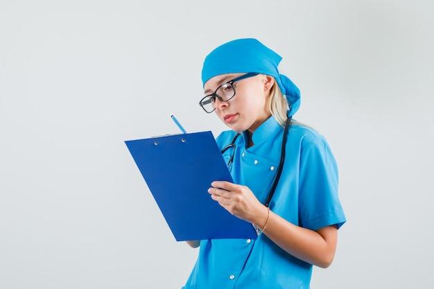 青い制服、眼鏡、忙しそうに見えるクリップボードにメモを取る女性医師。