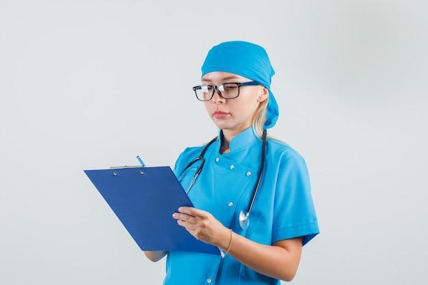 Женщина-врач делает заметки в буфере обмена в синей форме