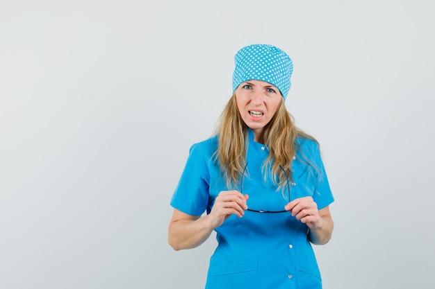 Женщина-врач снимает очки в синей форме и выглядит смущенным.