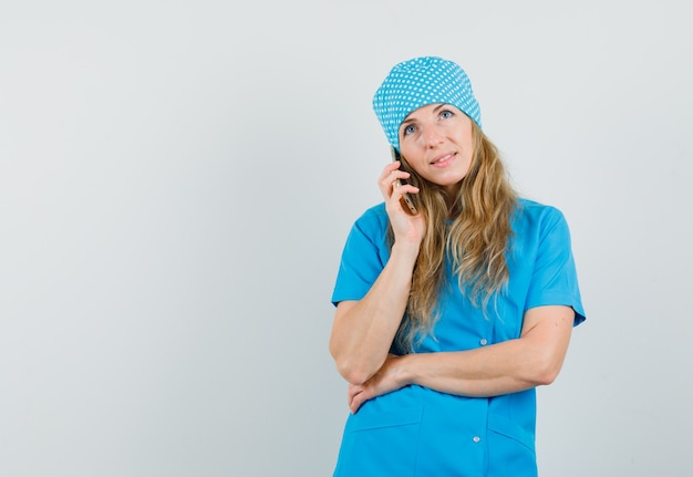 Female doctor talking on mobile phone in blue uniform and looking hopeful