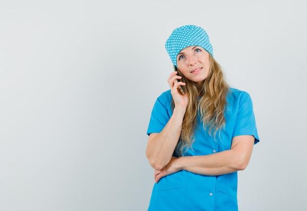 Женщина-врач разговаривает по мобильному телефону в синей форме и выглядит обнадеживающей