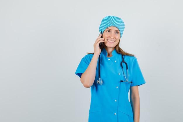 Женщина-врач разговаривает по смартфону и улыбается в синей форме