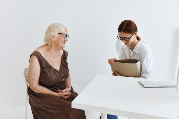 Женщина-врач разговаривает с диагностикой здоровья пожилой женщины