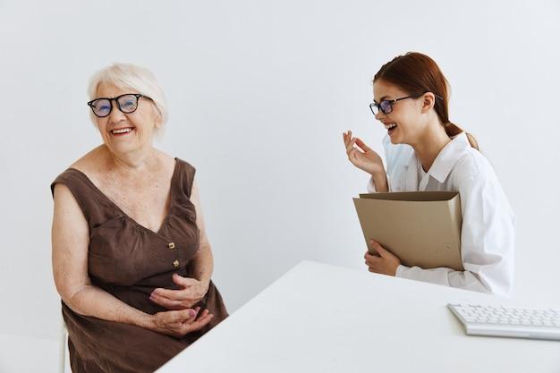 Женщина-врач разговаривает с пожилой женщиной, профессиональное лечение