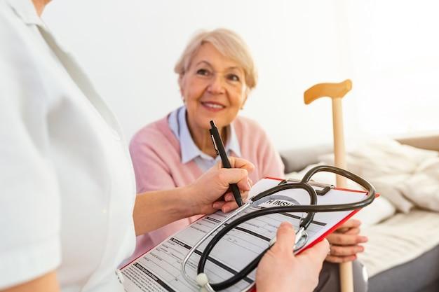Женский доктор разговаривая с старшим пациентом