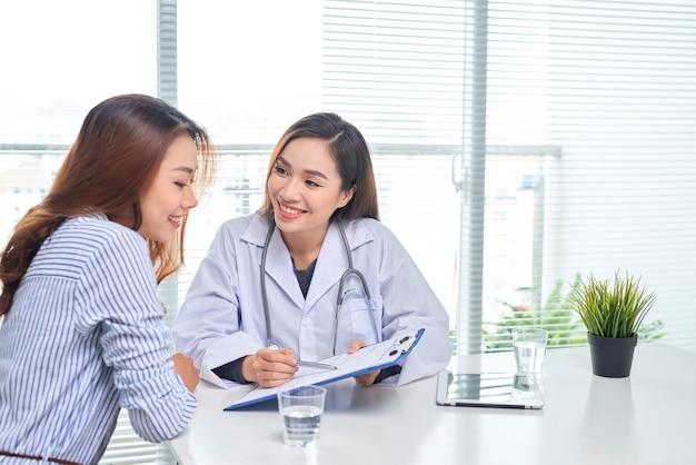 Женщина-врач разговаривает с пациенткой в больничном кабинете, делая запись в медицинской карте пациента на столе. здравоохранение и медицинское обслуживание.