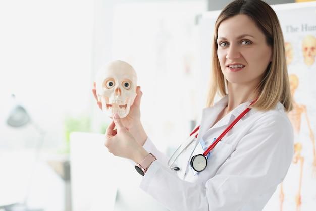 인간의 두개골 근접 촬영을 들고 여성 의사 선생님