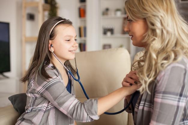 Женщина-врач учит ее маленькую девочку использовать стетоскоп, чтобы слушать ее сердце.
