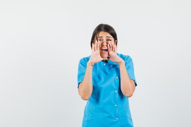 파란색 유니폼에 입 근처 손으로 비밀을 말하는 여성 의사
