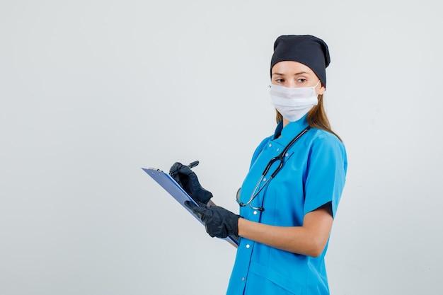 制服、手袋、マスクでクリップボードにメモを取りながら考える女医。