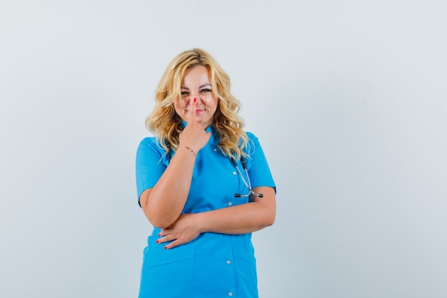 青い制服を着た指で彼女の鼻に触れる女医