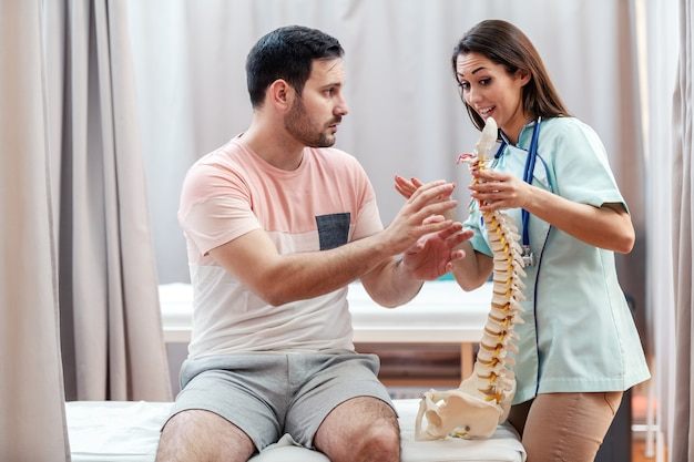 Female doctor in uniform holding spine model and talking to patient while patient showing her where he feeling pain.