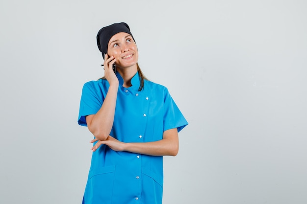Medico donna in uniforme che osserva in su mentre parla sullo smartphone e che sembra allegro