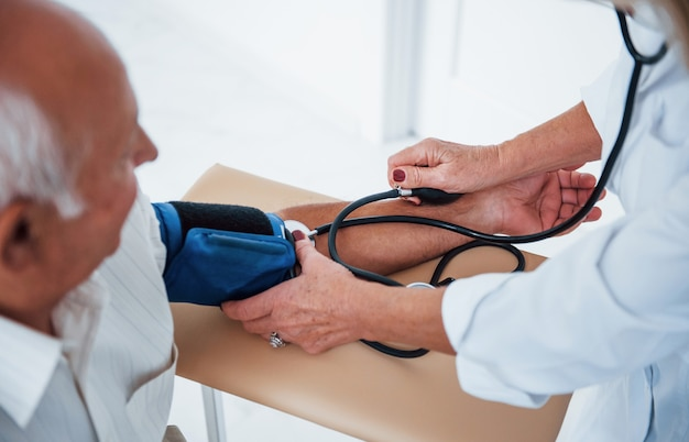 女医は眼圧計を使って年配の男性の血圧を測定します。