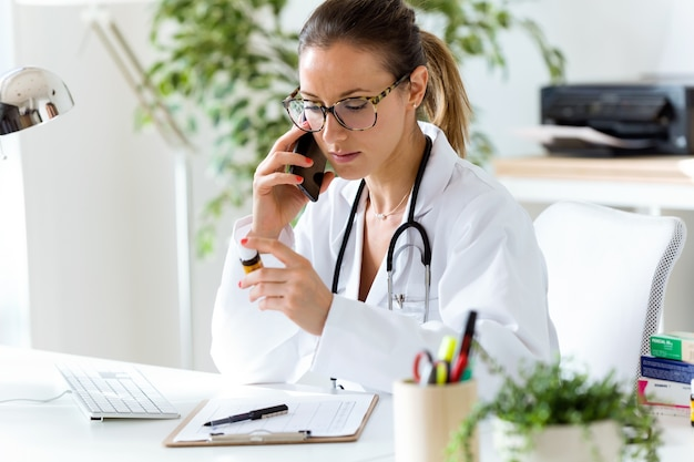 Женщина-врач, используя свой мобильный телефон в офисе.