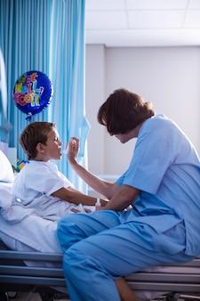 Женский доктор используя ингалятор на пациенте