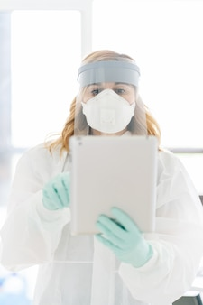 A female doctor using an ipad with safety equipment