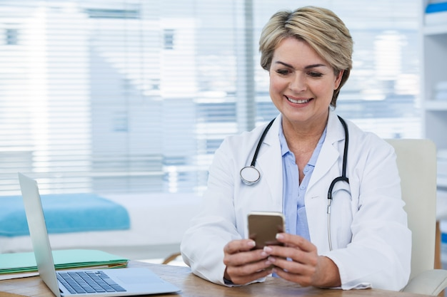 Female doctor using mobile phone with laptop on table
