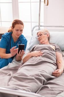 노인 여성을 위해 요양원에서 전화를 사용하는 여성 의사.