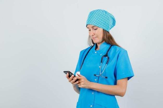 Medico donna utilizza lo smartphone in uniforme blu e sembra occupato. vista frontale.