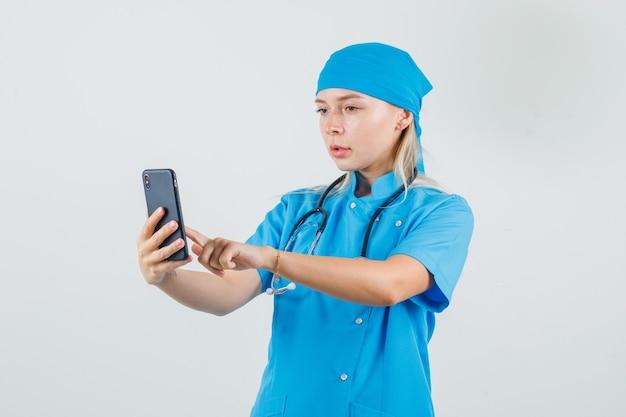 青い制服を着たスマホを使って忙しそうな女医。