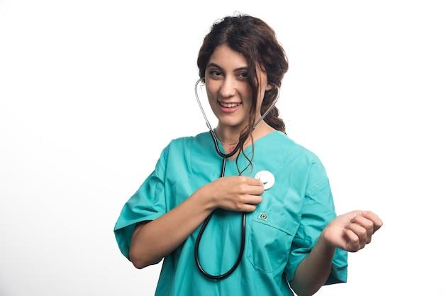 Женщина-врач с помощью стетоскопа на белом фоне. фото высокого качества