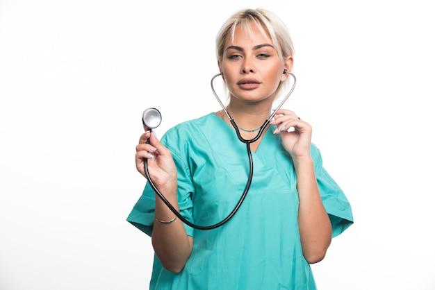 흰 벽에 청진기를 사용하는 여성 의사.