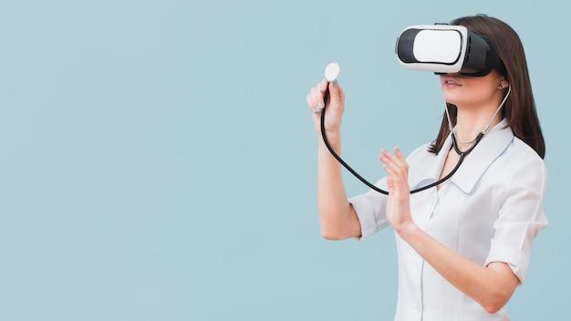 Medico femminile che per mezzo dello stetoscopio e della cuffia avricolare di realtà virtuale con lo spazio della copia
