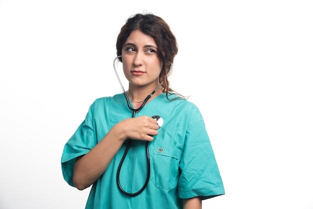 Medico donna utilizzando uno stetoscopio su sfondo bianco. foto di alta qualità